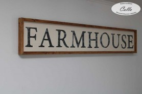tabula s napisom FARMHOUSE na stenu s ramom