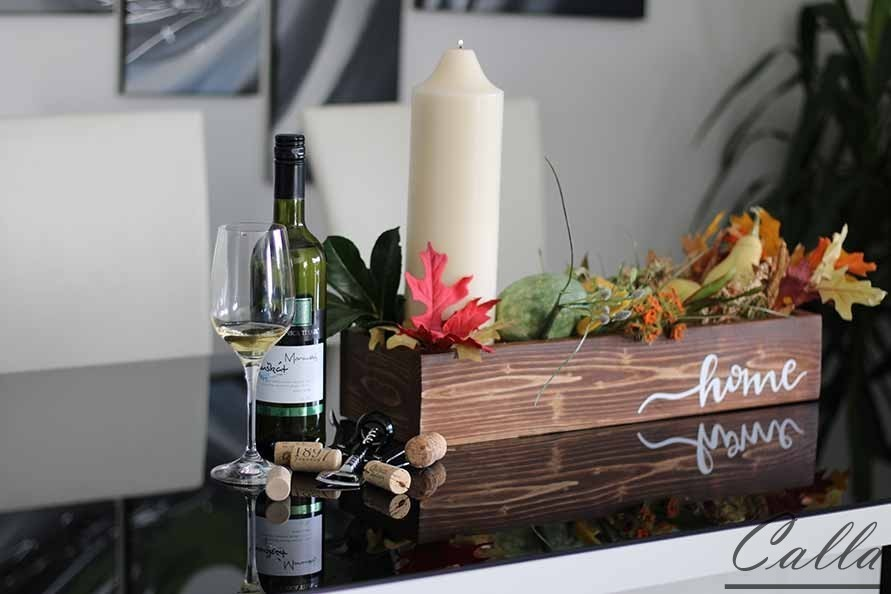 drevena tacka s flasou vina na stole