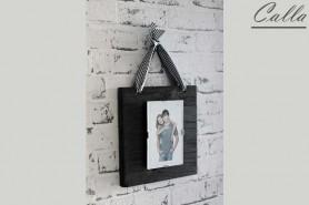 drevený fotorám na stene so stuhou