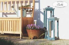 drevená lucerna v sivej farbe vedla rustikálnej lavičky
