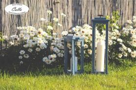 ručne vyrobená lucerna v záhone kvetov a so sviečkami